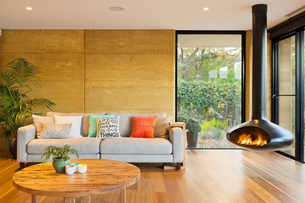 Internal rammed earth feature wall in modern living room with floating fireplace