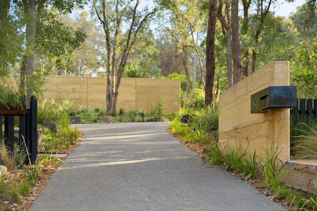 Rammed earth letter box post and landscaping entry walls