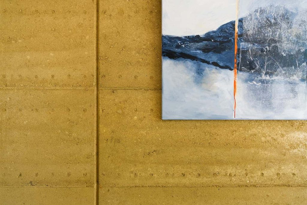 Close up of the natural texture and warm tones of an internal rammed earth wall