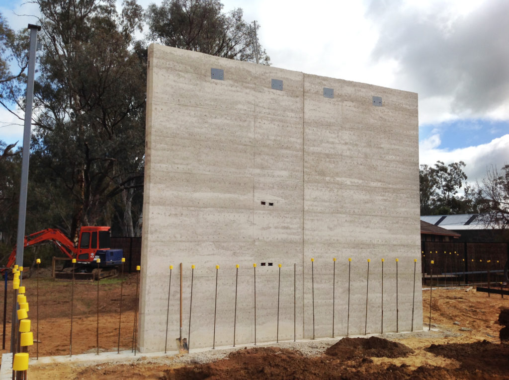 Image of cooler toned grey rammed earth wall just after construction